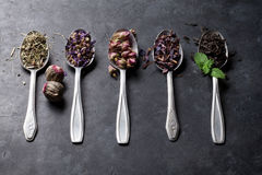 Assortment of dry tea in spoons on stone table Stock Photos