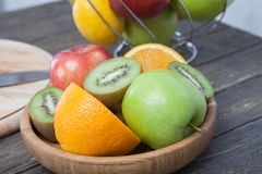 Assortment of exotic fruits close-up: kiwi, red and green apple, oranges and lemon on wooden table. Green grocery. Healthy and vegan food. Delicious fruits Royalty Free Stock Photos