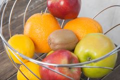 Assortment of exotic fruits close-up: kiwi, red and green apple, oranges and lemon on wooden table. Green grocery. Healthy and vegan food. Delicious fruits Stock Photos