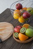 Assortment of exotic fruits close-up: kiwi, red and green apple, oranges and lemon on wooden table. Green grocery. Healthy and vegan food. Delicious fruits Royalty Free Stock Photography