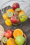 Assortment of exotic fruits close-up: kiwi, red and green apple, oranges and lemon on wooden table. Green grocery. Healthy and vegan food. Delicious fruits Stock Images