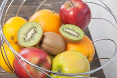Assortment of exotic fruits close-up: kiwi, red and green apple, oranges and lemon on wooden table. Green grocery. Healthy and vegan food. Delicious fruits Stock Photo