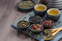 Assortment of fragrant dried teas and green tea on wooden table Royalty Free Stock Images