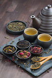 Assortment of fragrant dried teas and green tea on wooden table Stock Photos