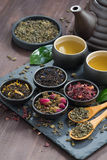 assortment of fragrant dried teas and green tea on wooden table Stock Photo