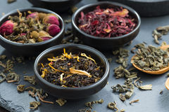 Assortment of fragrant dry tea in ceramic bowls Stock Images