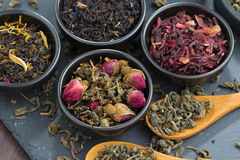 Assortment of fragrant dry tea in ceramic bowls, top view Royalty Free Stock Images
