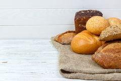 Assortment of fresh baked bread on wood table Stock Images