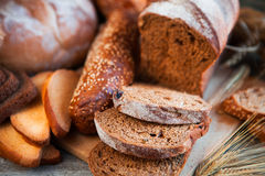 Assortment of fresh baked bread on wooden table background Stock Photo