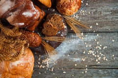 Assortment of fresh baked bread on wooden table background Stock Photos