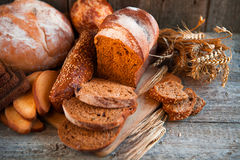 Assortment of fresh baked bread on wooden table background Stock Image