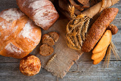 Assortment of fresh baked bread on wooden table background Royalty Free Stock Images