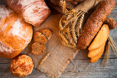 Assortment of fresh baked bread on wooden table background Royalty Free Stock Photos