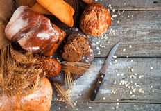 Assortment of fresh baked bread on wooden table background Stock Images