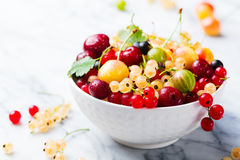 Assortment fresh berries in white bowl. Copy space. Assortment of fresh berries in white bowl. Marble background. Copy space Stock Photo