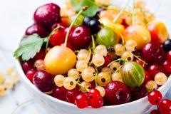 Assortment of fresh berries in white bowl. Marble background. Assortment of fresh berries in white bowl. Marble background Royalty Free Stock Image