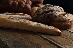 Assortment of fresh bread on a wooden background Stock Images