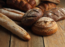 Assortment of fresh bread on a wooden background Royalty Free Stock Photos