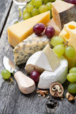 Assortment of fresh cheeses, grapes and walnuts, vertical Royalty Free Stock Photo