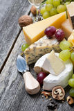 Assortment of fresh cheeses, grapes and walnuts on wooden table Royalty Free Stock Images
