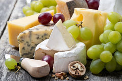 Assortment of fresh cheeses and grapes on a wooden background Royalty Free Stock Images