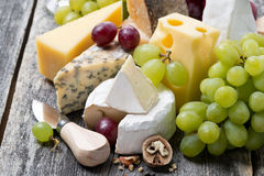 Assortment of fresh cheeses and grapes on a wooden background Royalty Free Stock Photos