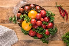 Assortment of fresh colorful tomatoes in oval bowl royalty free stock photography