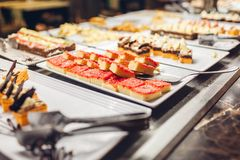 Assortment of fresh desserts displayed in hotel buffet. Variety of cakes in canteen ready for dinner royalty free stock image