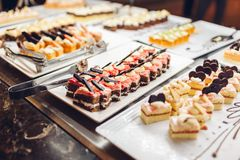Assortment of fresh desserts displayed in hotel buffet. Variety of cakes in canteen ready for dinner stock photo