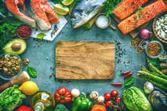 Assortment of fresh fish with aromatic herbs, spices and vegetab Royalty Free Stock Image