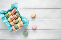 Stack of French Pink Strawberry Macarons. Assortment of fresh french macarons packaged in a pretty white wooden box with blue tissue on a white rustic table royalty free stock images