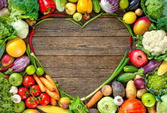 Assortment of  fresh fruist and vegetables in heart shape. Assortment of  fresh fruits and vegetables in heart shape on wooden background Stock Photos