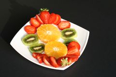 Assortment of Fresh Fruits. Sliced in on a white plate on a black background Stock Photos
