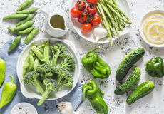 Assortment of fresh garden vegetables - asparagus, broccoli, beans, peppers, tomatoes, cucumbers, garlic, green peas on a light ba Stock Photo