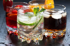Assortment of fresh iced fruit drinks on a dark background. Closeup royalty free stock photography