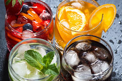 Assortment of fresh iced fruit drinks on a dark background. Top view, horizontal stock photo