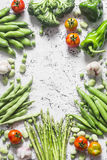 Assortment of fresh organic vegetables with copy space on a light background, top view. Asparagus, broccoli, green beans, peas, be Stock Photos