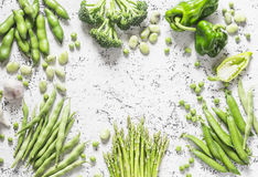 Assortment of fresh organic vegetables with copy space on a light background, top view. Asparagus, broccoli, green beans, peas, be Stock Images