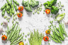 Assortment of fresh organic vegetables with copy space on a light background, top view. Asparagus, broccoli, green beans, peas, be Royalty Free Stock Photo