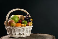 Assortment of fresh raw fruits in wicker basket. On wooden stump  on black background. Healthy eating concept Royalty Free Stock Photo