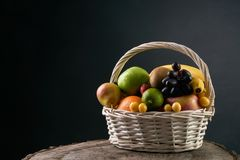 Assortment of fresh raw fruits in wicker basket. On wooden stump  on black background. Healthy eating concept Royalty Free Stock Images