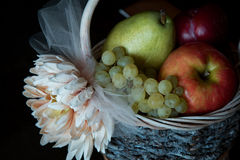 Assortment of fresh raw fruits in wicker basket on black background. Healthy eating concept Stock Photography