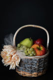 Assortment of fresh raw fruits in wicker basket on black background. With copy space. Assortment of fresh raw fruits in wicker basket on black background Royalty Free Stock Photo