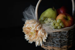 Assortment of fresh raw fruits in wicker basket on black background. With copy space Stock Images