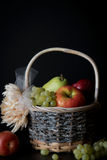 Assortment of fresh raw fruits in wicker basket on black background. With copy space. Assortment of fresh raw fruits in wicker basket on black background Stock Photography