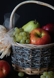 Assortment of fresh raw fruits in wicker basket on black background. Healthy eating concept Stock Photos