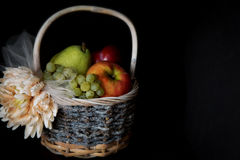 Assortment of fresh raw fruits in wicker basket on black background. With copy space. Assortment of fresh raw fruits in wicker basket on black background Stock Images