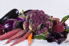 Assortment of fresh raw purple homegrown vegetables on dark wooden table. Cauliflower, eggplant  beets  carrots potatoes  plums basil  onions garlic  beans Royalty Free Stock Images