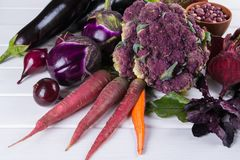Assortment of fresh raw purple homegrown vegetables on dark wooden table. Cauliflower  eggplant  beets  carrots  potatoes  plums basil  onions  garlic  beans Stock Photo