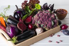 Assortment of fresh raw purple homegrown vegetables on dark wooden table. Cauliflower eggplant  beets  carrots  potatoes  plums  basil  onions garlic  beans Royalty Free Stock Photo